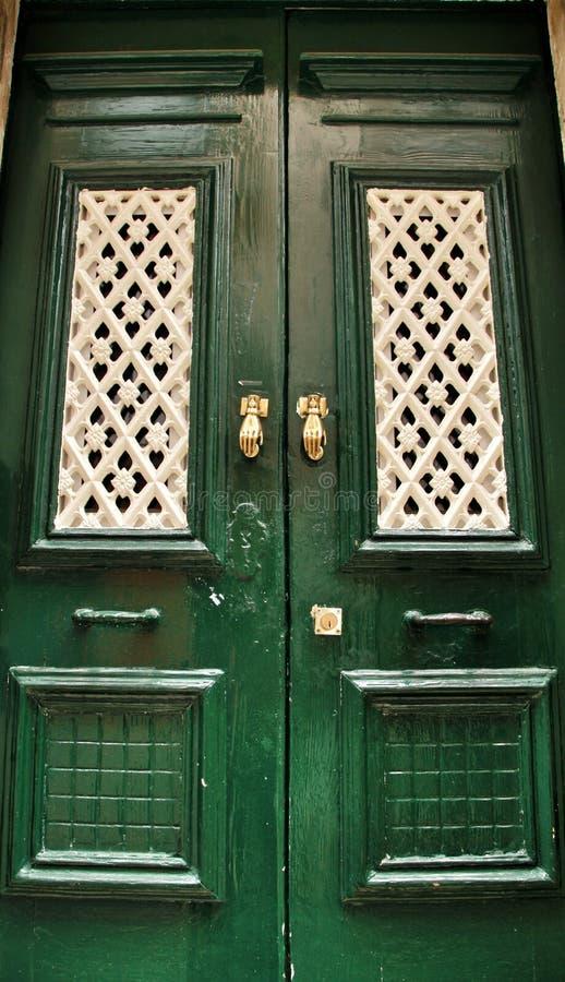 Heurtoirs de porte avec la forme de main sur la porte en bois verte images libres de droits
