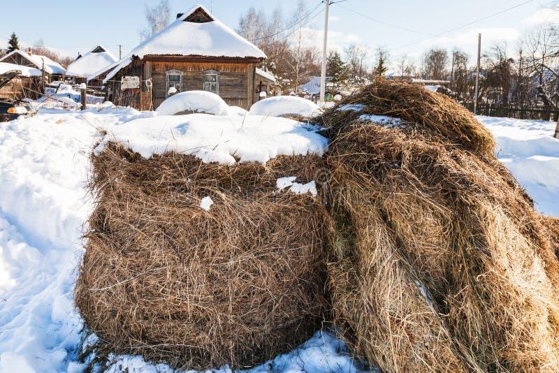 Heuschober auf schneebedeckter Straße im Dorf lizenzfreie stockbilder