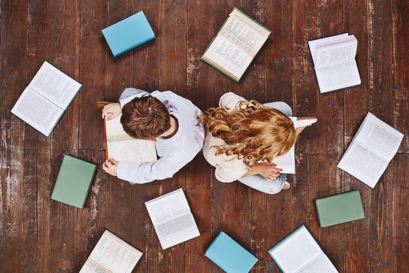 Heute ein Leser, morgen ein Führer Kinder, die nahe Büchern, beim Ablesen sitzen Sie halten Bücher in den Händen stockfoto