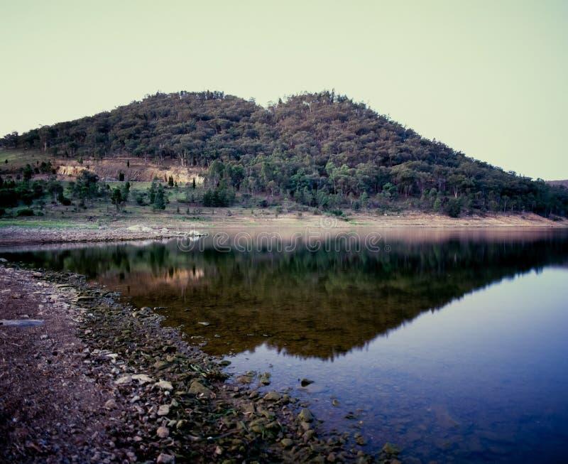 Heuvel en landschap die in de Dam Nieuw Zuid-Wales Australië van meerwindamere bij blauw uur nadenken stock foto's