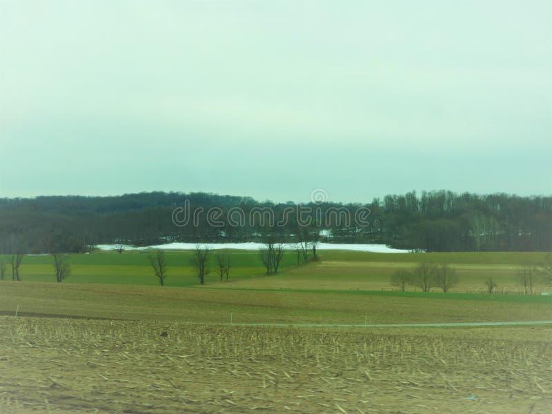 Heuvelig gebied in Pennsylvania met sneeuw en bomen in de afstand stock foto's