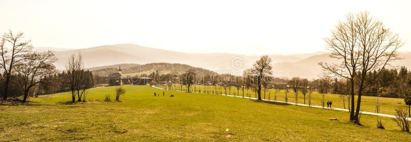 Heuvelig landschap van Jizera-Bergen rond Prichovice-dorp Groene weiden met boomsteeg en kleine landelijke kerk stock afbeelding