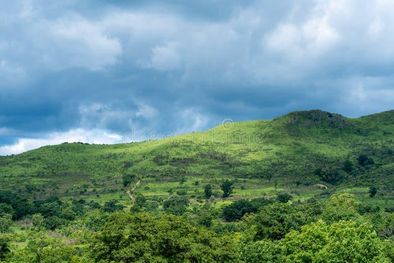 Heuvellandschap in het zonlicht tegen de hemel met donderwolken stock foto
