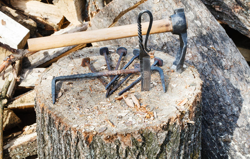 Hew ax and forged hardware on wooden deck. Near village smithy royalty free stock photography