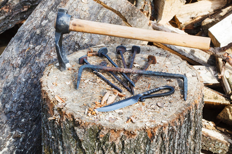 Hew axe and metal hardware on wooden block. Near rustic smithy stock photo