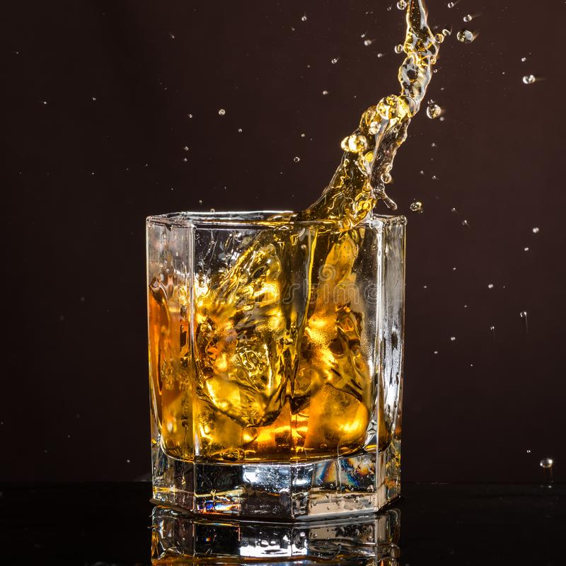Hexagonal glass of whiskey with ice and splashes from an abandoned and falling ice cube royalty free stock photos