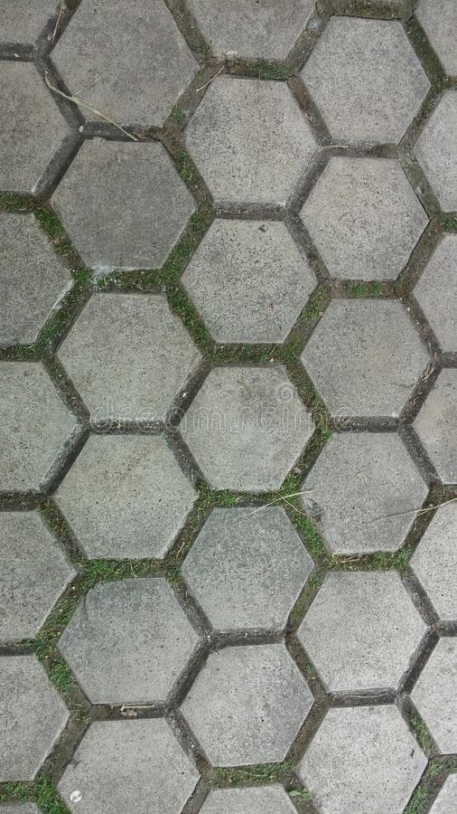 Hexagonal stone texture paving. Stone paving with moss and dirt between the hexagonal pieces stock images