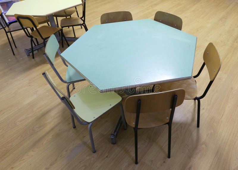 Hexagonal table with the chairs of a school stock image