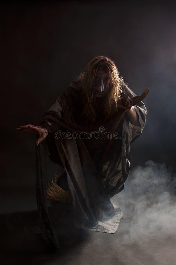Hexe auf Besen im Nebel stockbild