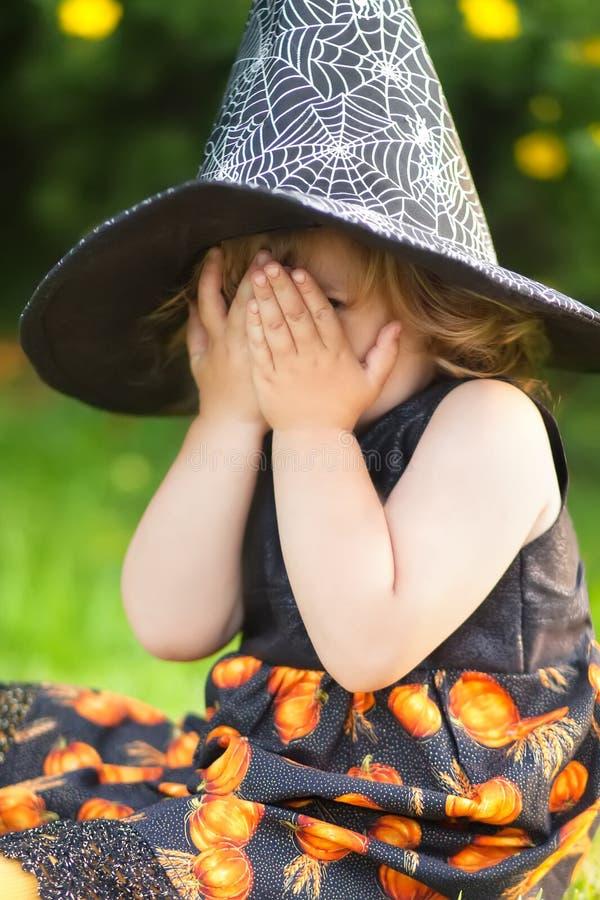 Hexe des kleinen Mädchens im schwarzen spitzen Hut, ängstlich von Halloween lizenzfreies stockfoto