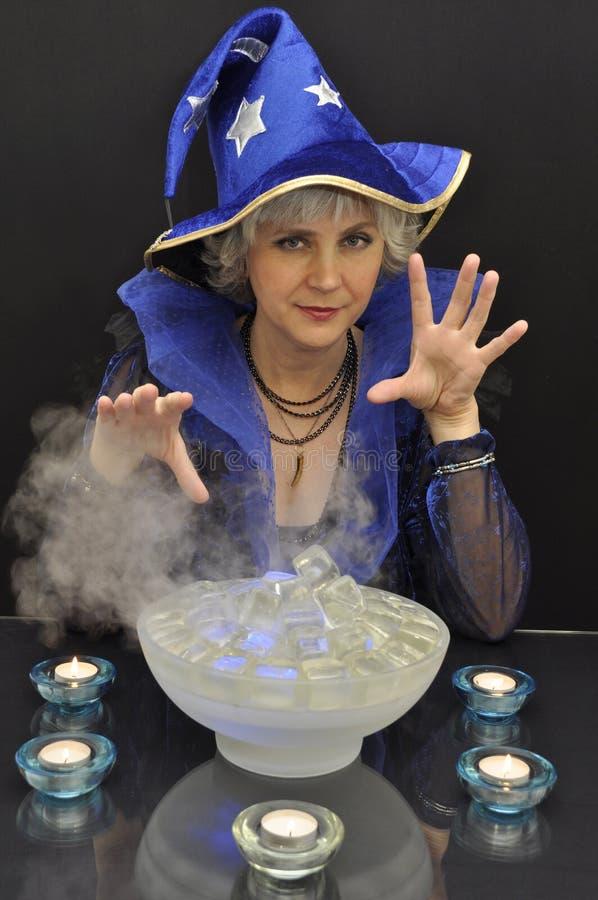 Hexe im blauen Hut mit magischen Kristallen und Kerzen lizenzfreies stockfoto