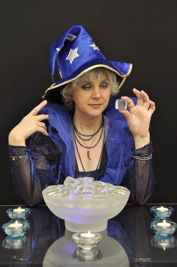 Hexe im blauen Hut mit magischen Kristallen und Kerzen stockbilder