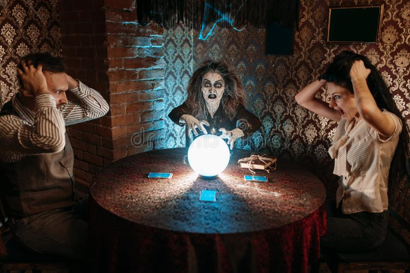 Hexe liest furchtsamen Bann über einer Glaskugel stockfotos