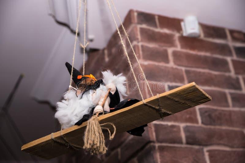 Hexe mit Besen, traditionelle Andenkenpuppe der Marionette spielen Sie Hexe auf einem Schwingeninnendetail für Halloween Hallowee stockfotos