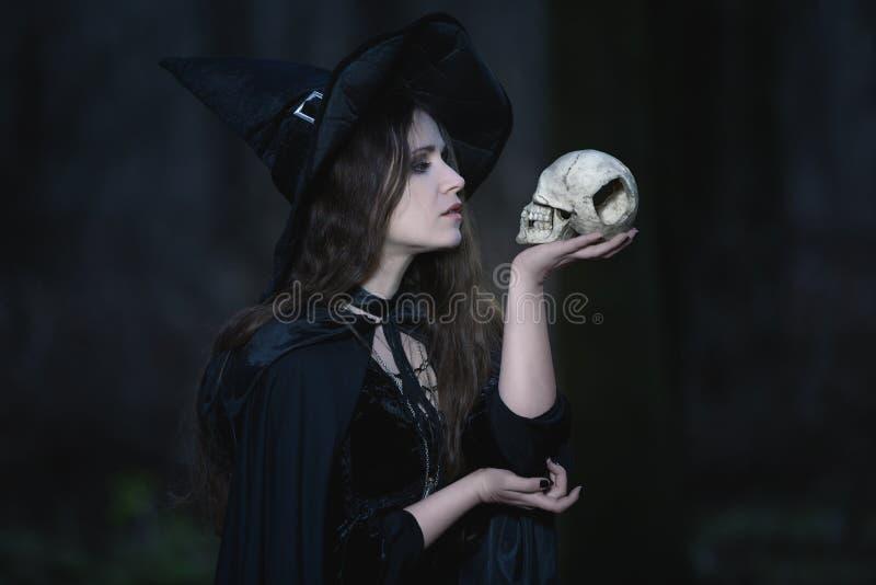 Hexe mit einem Schädel stockfoto