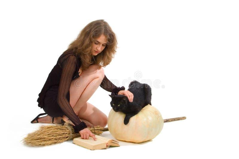 Hexe mit Kürbis, Besen und schwarzer Katze stockfotografie