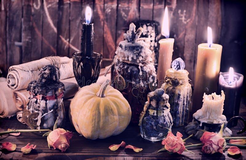Hexenflaschen mit Kürbis, schwarzen Kerzen und Papierrollen stockfoto