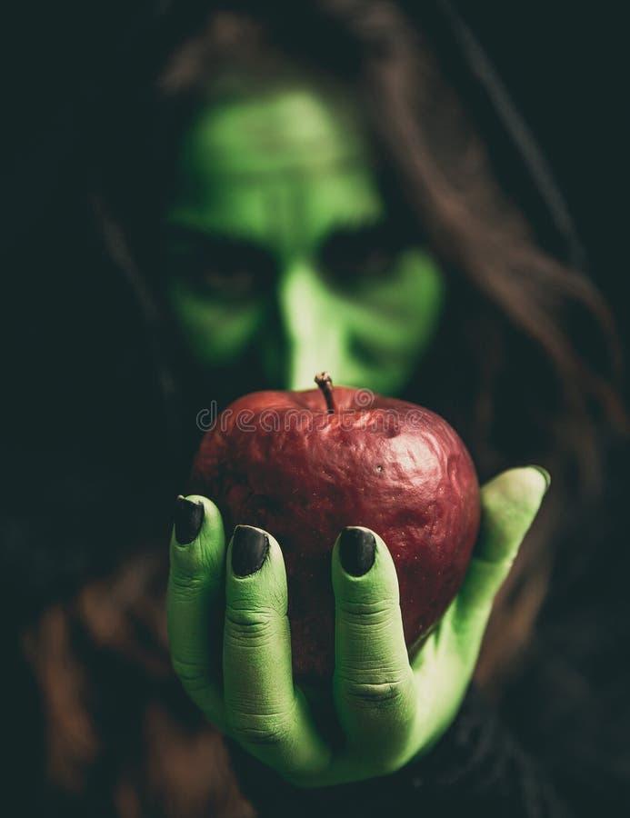 Hexenhand mit Apfel lizenzfreie stockfotos