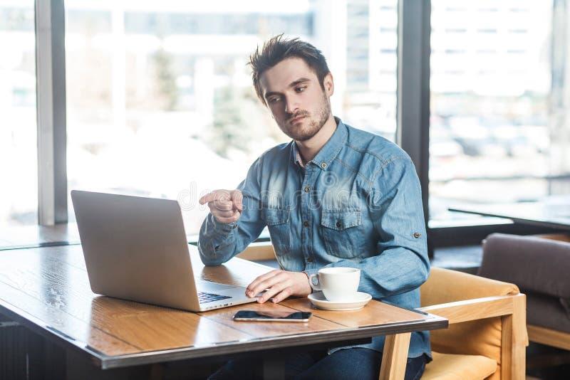 Hey вы! Портрет сердитого несчастного молодого бизнесмена в рубашке голубых джинсов сидит в кафе и имеющ плохое настроение учить стоковое фото