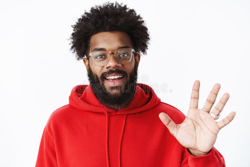 Hey cumprimentos O retrato da obtenção afro-americano sociável amigável e que parte do homem conhece a equipe nova que acena com  fotos de stock royalty free