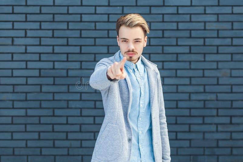 Hey dig Stående av den allvarlig eller för ilska stiliga unga blonda mannen i tillfällig stil som står, pekar och ser kameran med arkivbild