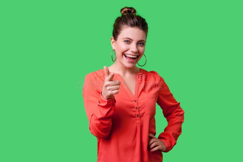Hey du! Porträt einer schönen positiven jungen Frau mit Bun-Frisur, großen Ohrringen und roter Bluse isoliert auf grünem Hintergr lizenzfreies stockfoto