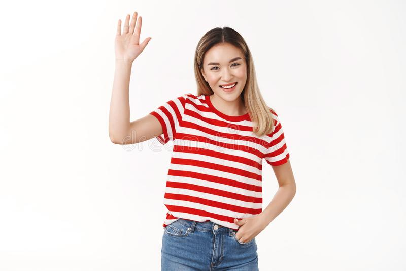 Hey friends how hanging. Friendly outgoing sociable cute asian blond girl raise hand waving palm hi hello gesture royalty free stock images