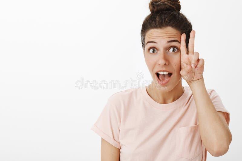 Hey frio e para apreciar a vida Mulher europeia à moda relaxado e carismática bonita despreocupada no levantamento cor-de-rosa do foto de stock