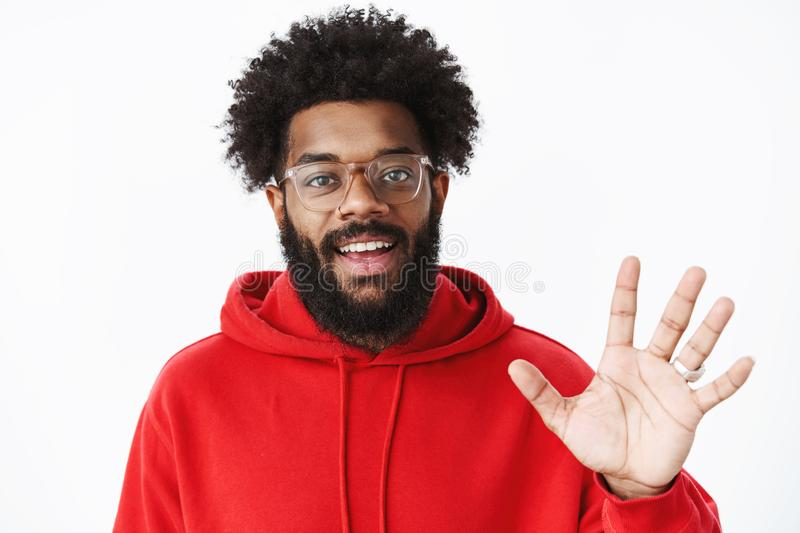 Hey greetings. Portrait of friendly and outgoing sociable african american man getting know new team waving with palm. And smiling at camera as saying hello royalty free stock photos