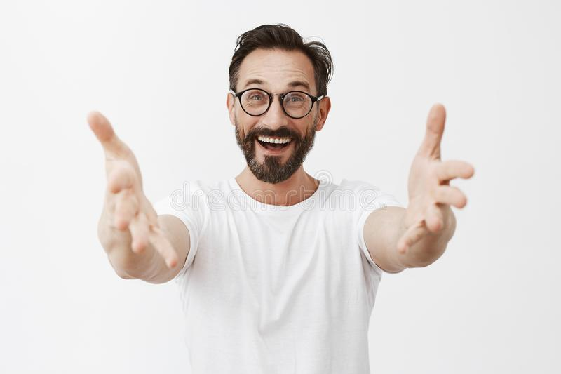 Hey long time no see. Surpirsed happy and joyful old friend in glasses with beard and moustache, pulling hands towards. Camera to greet mate and give warm hug royalty free stock image