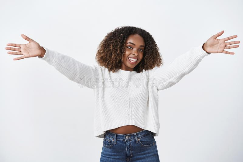 Hey nice see you. Charming friendly outgoing cute african american girl stretch raised hands wanna embrace say hi friend. Smiling pleasantly cuddling welcoming royalty free stock photography