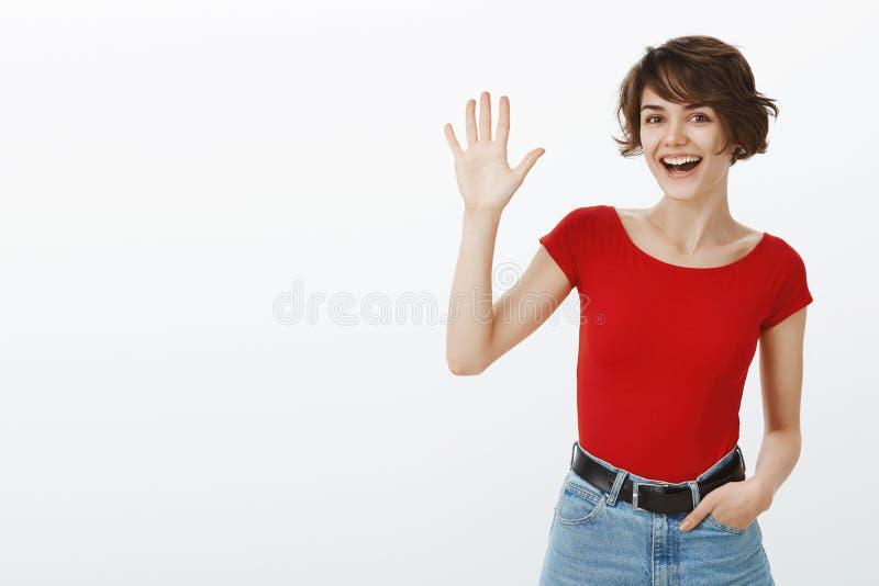 Hey o que está acima O corte de cabelo curto da menina europeia amigável alegre sociável atrativa que acena a palma aumentada diz imagens de stock