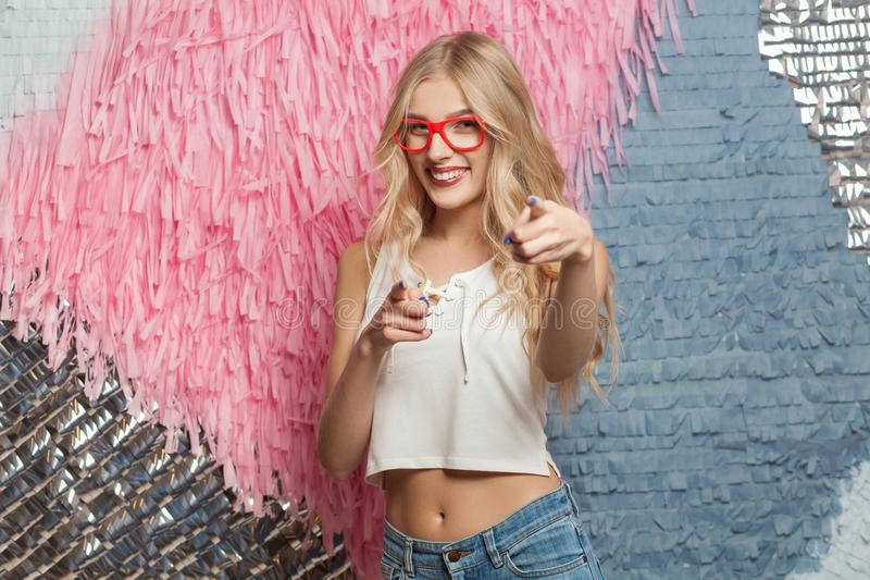 Hey u! Het meisje van het gelukblonde in rode glazen, die vingers richten stock fotografie