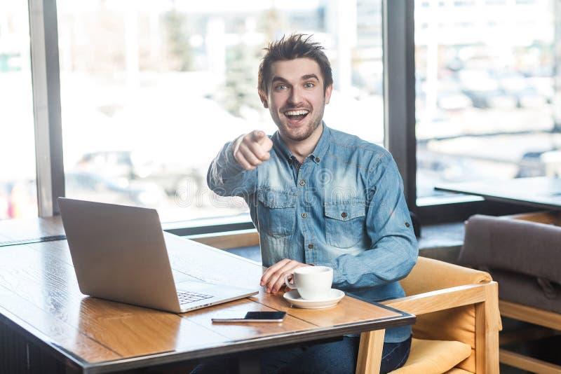 Hey u! Het portret van gelukkige positieve gebaarde jonge freelancer in jeansoverhemd zit in koffie en werkt aan laptop met stock foto's