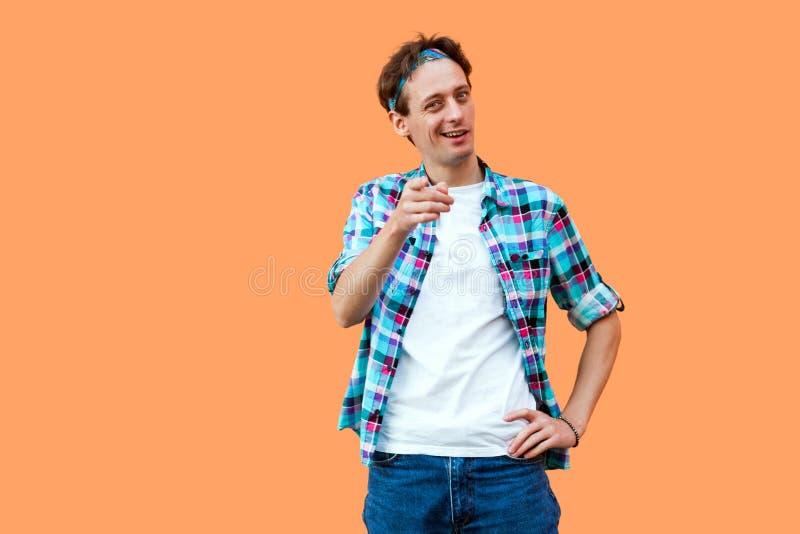Hey u Portret van de grappige jonge mens in toevallige blauwe geruite overhemd en hoofdband status bekijkend en richtend op camer stock foto's
