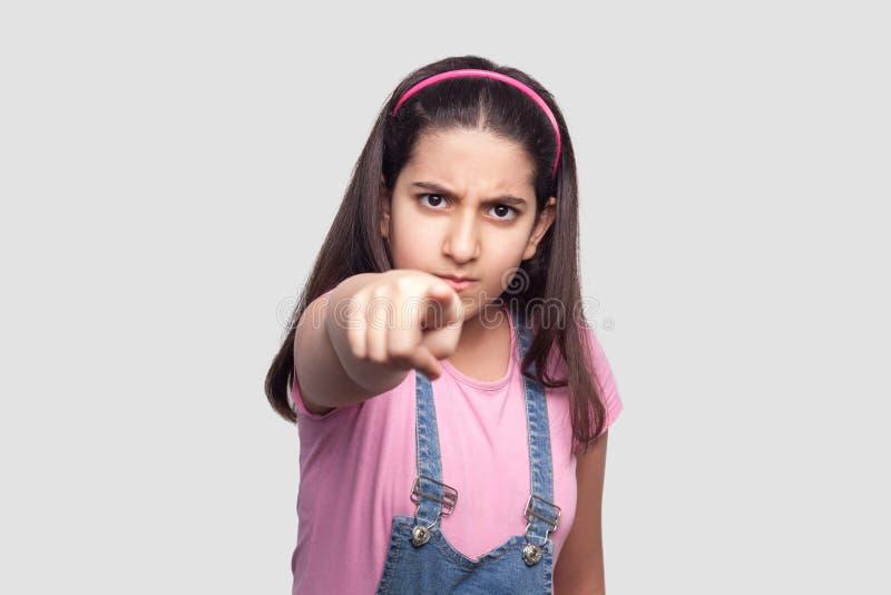 Hey u! Portret van ernstig donkerbruin jong meisje in toevallige stijl, roze t-shirt en blauwe denimoverall die, schuld, het kijk royalty-vrije stock afbeeldingen