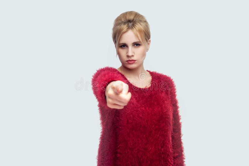 Hey u Portret van ernstige mooie jonge blonde vrouw in rode blouse die, en camera en schuld richten bekijken bevinden zich royalty-vrije stock afbeelding