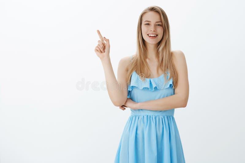 Hey você conseguiu vê-lo Mulher à moda nova feliz amigável e deleitada com cabelo justo no vestido de nivelamento azul que aponta imagem de stock royalty free