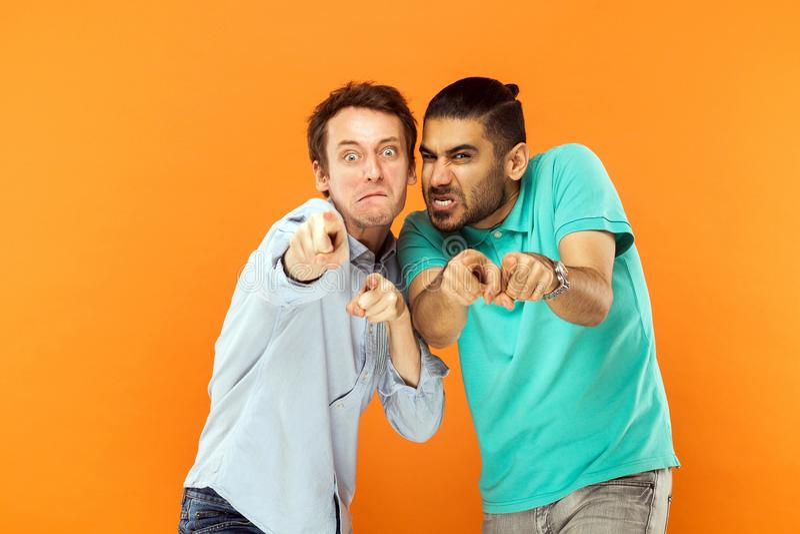 Hey você! Dois cômicos expressivos, fazendo caretas na câmera Apontando a aleta imagens de stock royalty free