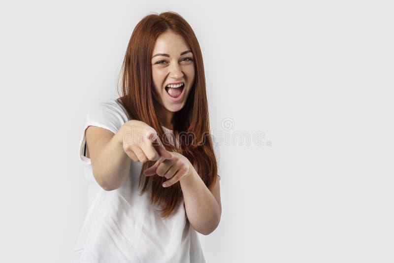 Hey você! Fêmea nova bonita que aponta à câmera com os dedos isolados no fundo cinzento foto de stock royalty free