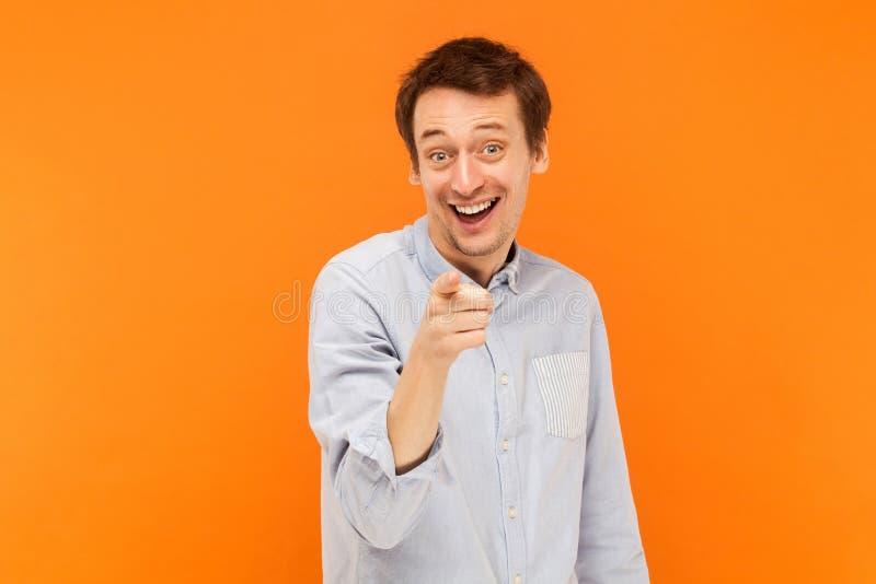 Hey você! Homem da felicidade que aponta o dedo na câmera e no smil toothy fotografia de stock