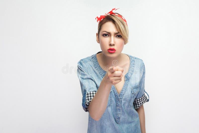 Hey você Retrato da jovem mulher bonita séria na camisa azul ocasional da sarja de Nimes com a composição e a faixa vermelha que  fotos de stock royalty free