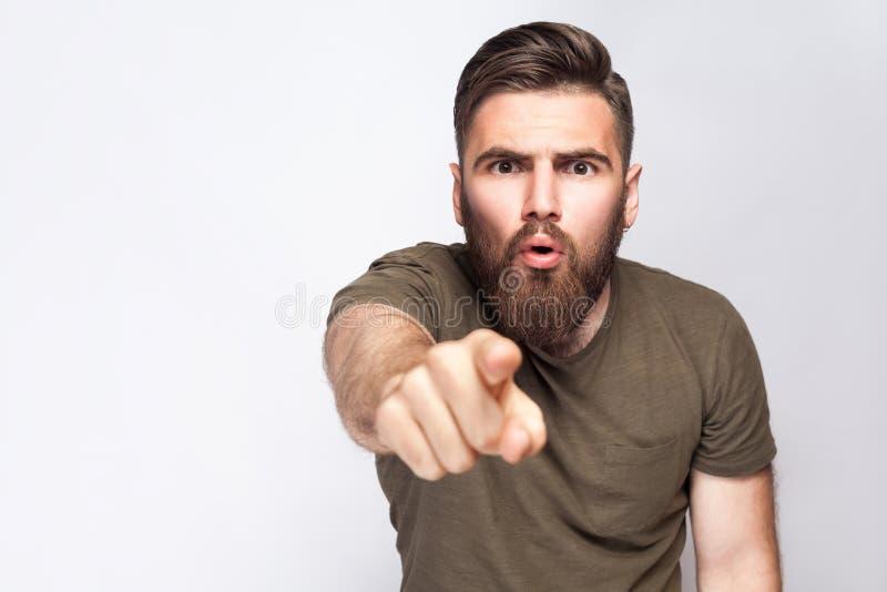 Hey você! Retrato do homem farpado entusiasmado surpreendido com obscuridade - camisa verde de t contra a luz - fundo cinzento fotografia de stock