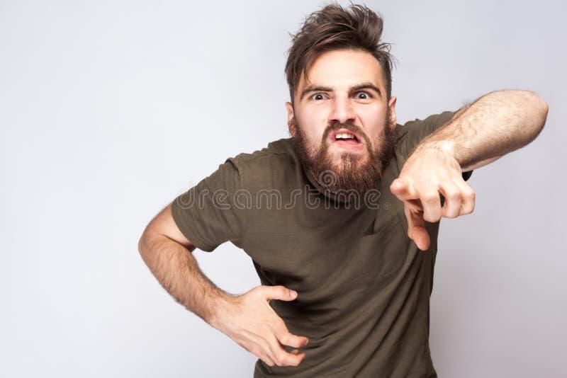 Hey você! Retrato do homem farpado irritado louco com obscuridade - camisa verde de t contra a luz - fundo cinzento imagens de stock royalty free