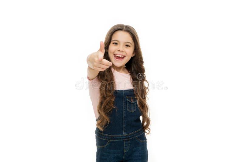 Hey voc? Apontar alegre do cabelo longo da menina para a frente Criança que aponta o fundo branco isolado câmera Mi?do que aponta fotografia de stock royalty free