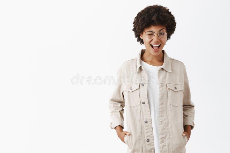 Hey voc? ? meu tipo Marimacho lésbica de pele escura seguro flirty bonito nos vidros e na camisa bege, pisc fotos de stock