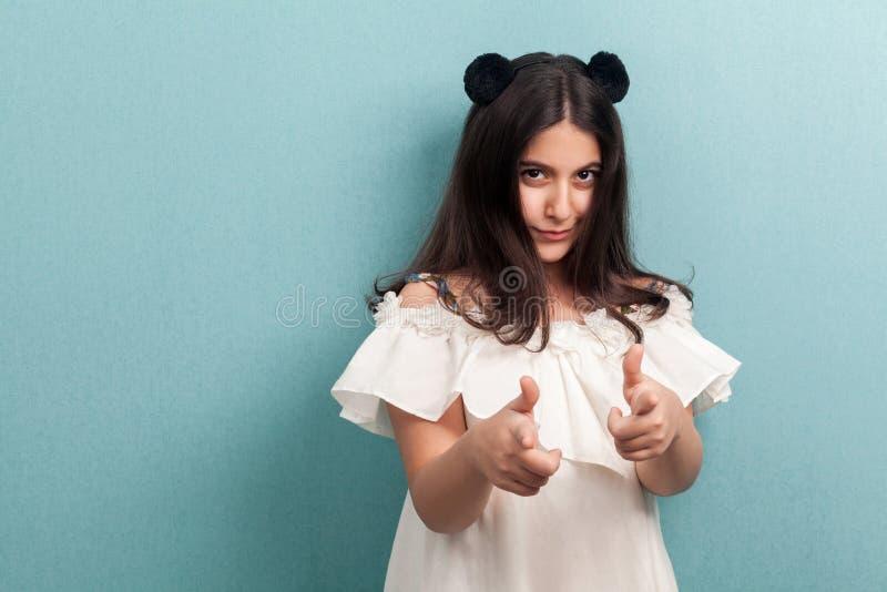 Hey voc? Retrato da moça moreno bonita com cabelo reto longo preto na posição branca do vestido que olha e que aponta em fotos de stock