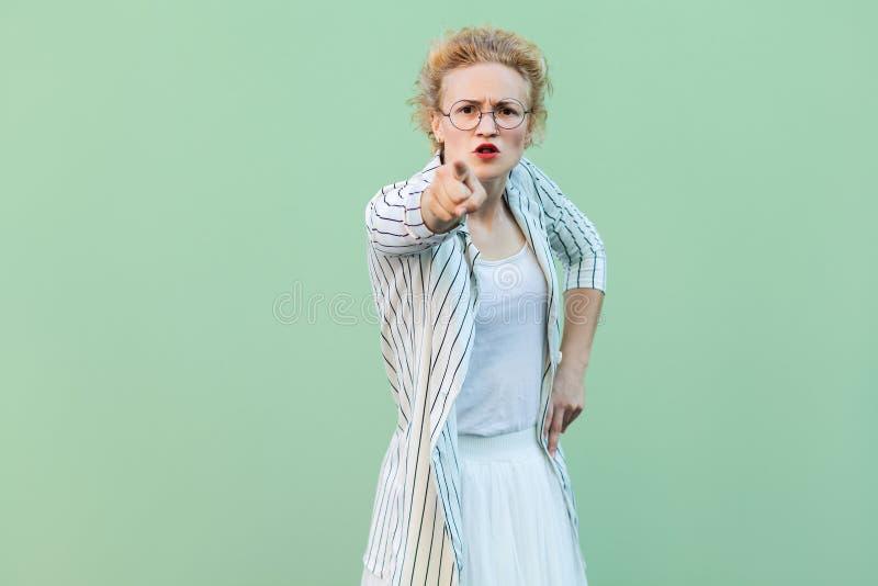 Hey voc? Retrato da mulher loura nova séria na camisa branca, na saia, e em estar listrado da blusa e dos monóculos, olhando e fotos de stock royalty free