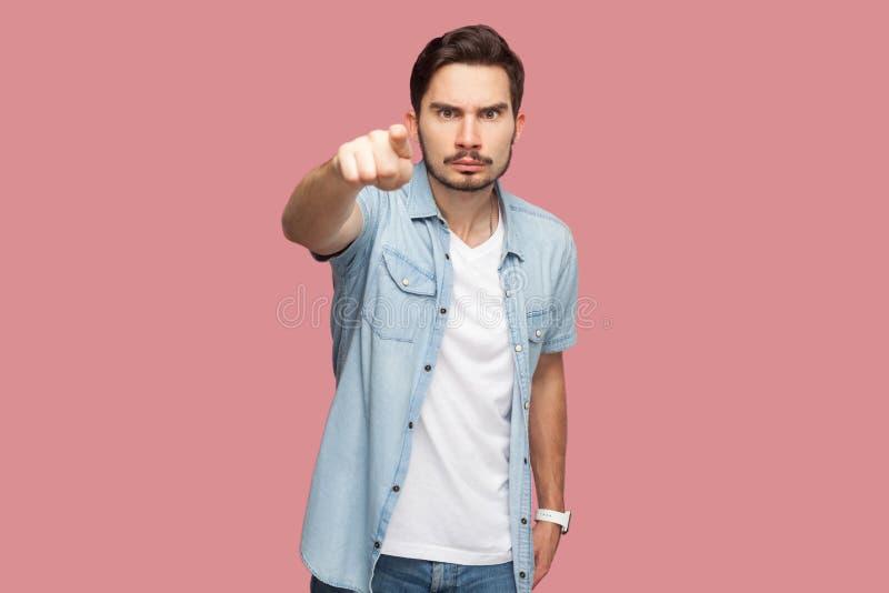 Hey voc? Retrato do homem novo farpado considerável sério na posição azul da camisa do estilo ocasional que aponta e que olha a c fotografia de stock