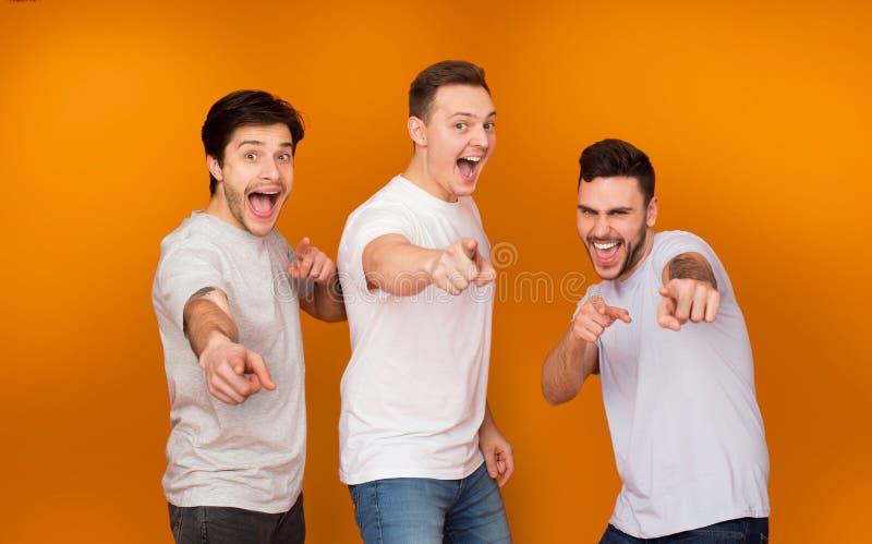 Hey, voi Amici felici che indicano le dita alla macchina fotografica fotografia stock libera da diritti